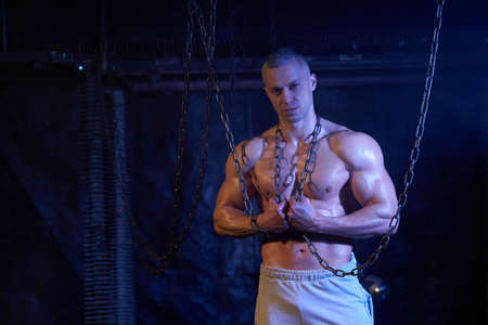 Young shirtless muscular man standing among metal chains, looking seriously at camera, copy space Archivio Fotografico