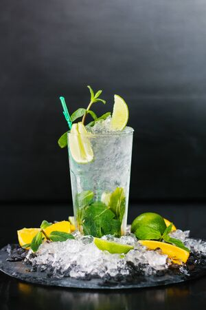 A glass of fresh Mojito. Lime, orange and mint. On a wooden background