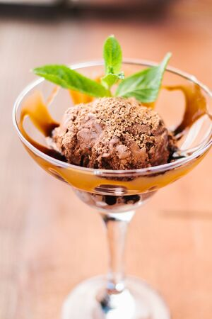 Chocolate ice cream in a glass with caramel topping