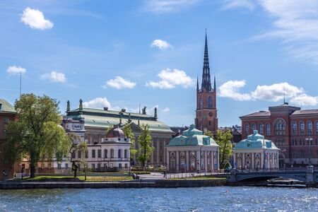 A Scenic View over Riddarholmen Sweden including a Church with a Blue Cloudy Sky photo