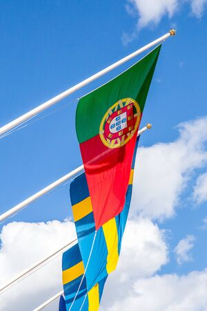 portugese: Portugese and Swedish Flags With Blue Sky in Background Stock Photo