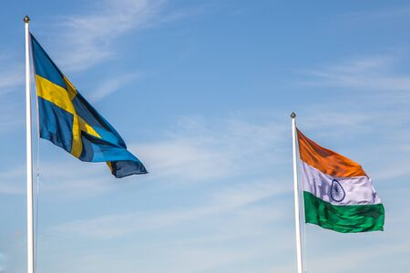 Swedish and Indian Flag Waving in Front of a Cloudy Blue Sky