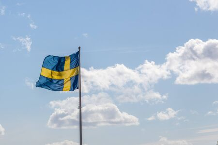 Swedish Flag Waving in the Midday Sun and a Blue Cloudy Sky in the Background photo