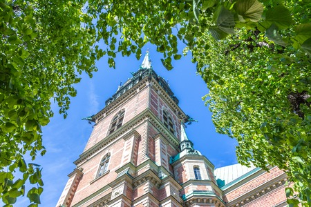 framed: Old Church Tyska Kyrkan In Gamla Stan Stockholm Standing Against a Blue Sky Framed By a Large Green Leafcover