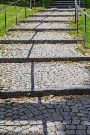 shadowy: Road Paved with Brick-Stones and Green Grass and a shadowy Leading Line Editorial