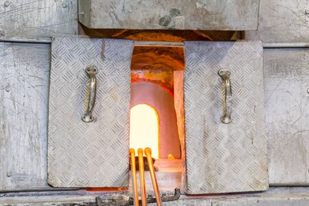 stove pipe: An Open Fiery Glassblowers Oven With Glass being Made Stock Photo