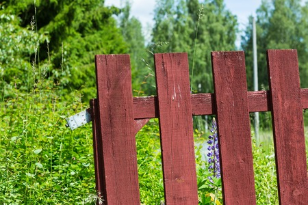 shrubbery: Red Painted Fence with Green Shrubbery and Bushes Behind Stock Photo