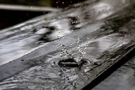 Rain drop splash in wooden floor bouncing and shaping water crown