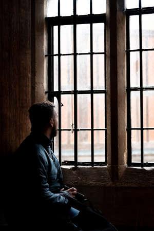 Rückansicht auf die Silhouette des Mannes, der durch ein altes helles Fenster schaut, träumt, sich ausruht, tief nachdenkt, während er ruhig wartet und der Tag vergeht.