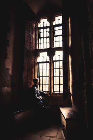 Rückansicht auf die Silhouette des Mannes, der in der Dunkelheit sitzt und durch ein altes helles Fenster mit einfallenden Lichtstrahlen schaut, träumt, ausruht, tief nachdenkt, während er ruhig wartet und der Tag vergeht.