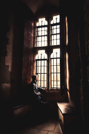 Rear view at silhouette of man sitting in the darkness looking through old bright window with incoming rays of light, dreaming, resting, thinking deeply while waiting quietly and day goes by.