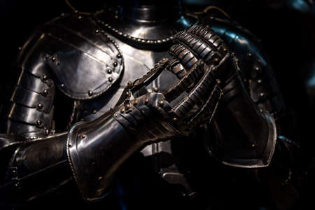 Medieval like armour suit and gloves shining in the dark.