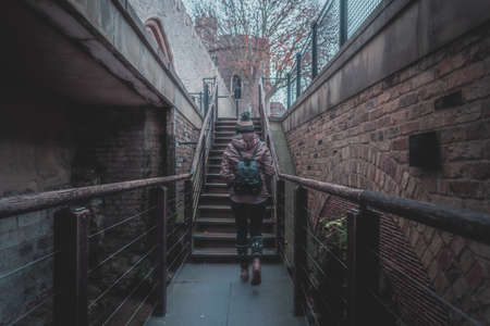 Rear view of silhouette of young woman walking through a stairway between old brick walls of an ancient castle on a cloudy and foggy day