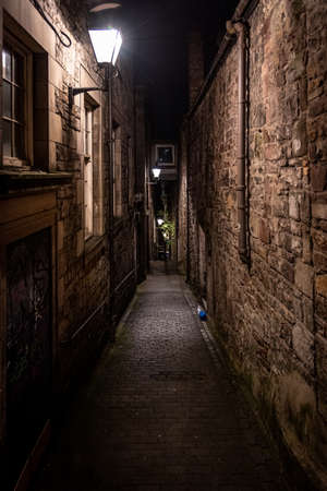 A dark creepy narrow European alley at night, surrounded by bricks and cobblestone. Illuminated only with some street lamps. Concept of scared or being alone and frightened Stock fotó