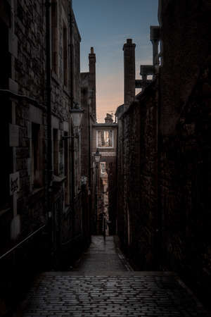 Narrow European alley, surrounded by bricks and cobblestone. Illuminated only with weak light from sunrise. Concept of scared or being alone and frightened.