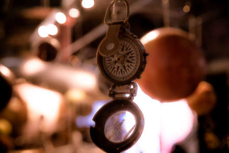 Beautiful bokeh of a compass hanging with lights and reflections in the background. Concept of being lost, freedom and pursuit of happiness