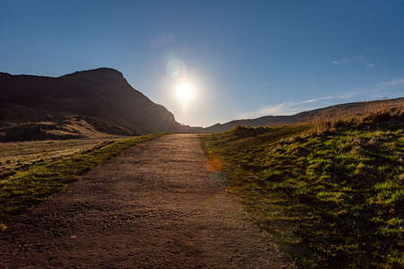 Path across the hills of Holyrood Park in Edinburgh, Scotland, with the sun rising bright at the end of the way. Popular destination for hiking and enjoying nature