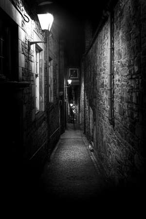A dark creepy narrow European alley at night, surrounded by bricks and cobblestone. Illuminated only with some street lamps. Concept of scared or being alone and frightened.