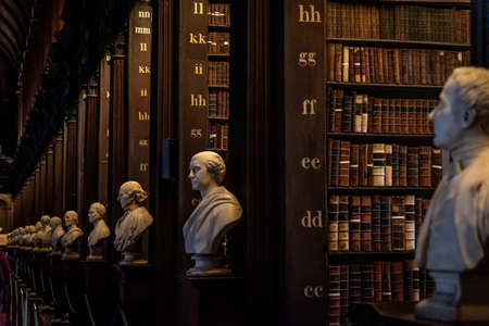 DUBLIN, IRELAND, DECEMBER 21, 2018: The Long Room in the Trinity College Library, home to The Book of Kells. Perspective view of the place, with large quantity of books and chest statues