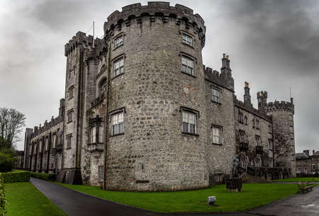 KILKENNY, IRELAND, DECEMBER 23, 2018: Kilkenny Castle seen from the corner of its entrance on a dramatic cloudy day Editorial