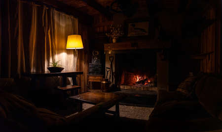 Interior of a wooden cozy and relaxing cabin with comfortable couches, country decoration, dimly lit by the fireplace and lamp. Concept of silence, tranquility, time to rest and relaxation Banque d'images