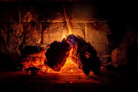 Gros plan des derniers instants de bois de chauffage brûlant dans le feu avec de faibles flammes légères et des ombres enveloppantes. Concept de tranquillité, de détente et de silence