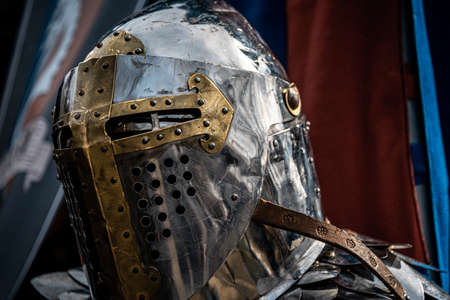 BUENOS AIRES, ARGENTINA, MAY 4, 2019: Shiny silver medieval iron knight helmet with a golden cross, full of scratches due to battles