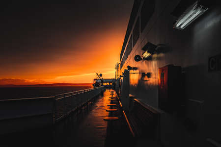 Deck of ferry sailing across the sea during last moments of a beautiful sunset with arriving land in the background. Concept of relaxation, adventure, freedom, luxury and leisure.