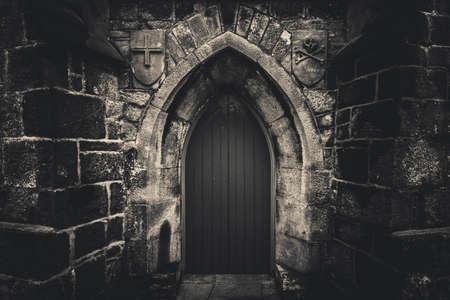 Porte en bois pointue effrayante dans un vieux bâtiment de mur en pierre humide avec croix, crâne et os des deux côtés en noir et blanc. Concept mystère, mort et danger. Banque d'images