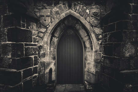 Scary pointy wooden door in an old and wet stone wall building with cross, skull and bones at both sides in black and white. Concept mystery, death and danger. Stock Photo