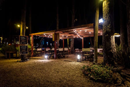 Night scene of an elegant outdoor bar illuminated by small hanging bulbs Imagens