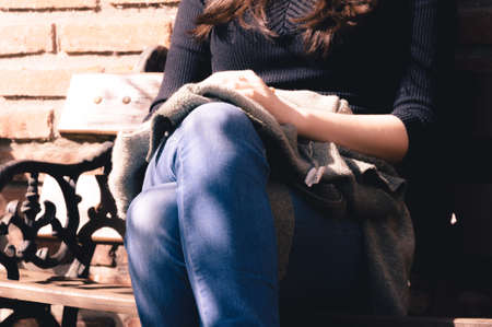 Close up of womans hands resting over her crossed legs while being sit on a bench in a sunny day Stock Photo