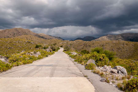 The golds road, San Luis, Argentina, which climbs steppe mountains. Seen from below while a heavy storm is coming