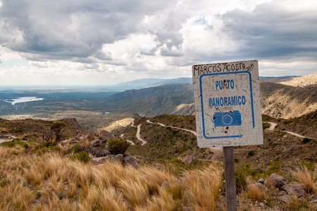 Rusty sign of viewpoint in Golds Road, San Luis, Argentina, which climbs steppe mountains with curved ascending ways Stock fotó