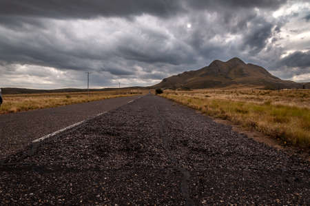 The old Golds Road at highest point in San Luis, Argentina, which climbs steppe mountains while a heavy storm is coming Stock fotó