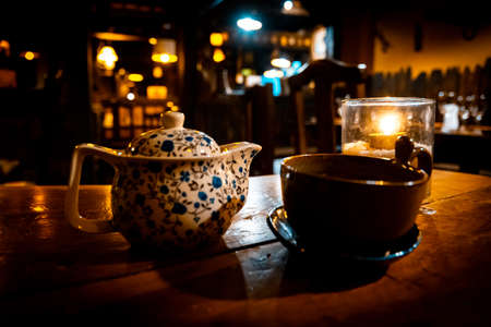 A teapot, a cup and a tealight inside a glass over a wooden table of a cozy Irish pub