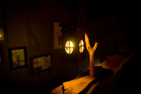 Decorative handcrafted wooden lantern with a candle inside dimly glowing in the dark