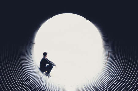 Silhouette of a man looking pensively at the edge of a tunnel through a white void. Space to place text. Concept