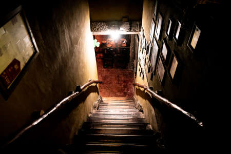 Dramatic point of view of scary stairs from upside into darkness of interior of old pub