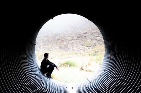 Silhouette of a man looking pensively at the edge of a tunnel through the mist of the mountain