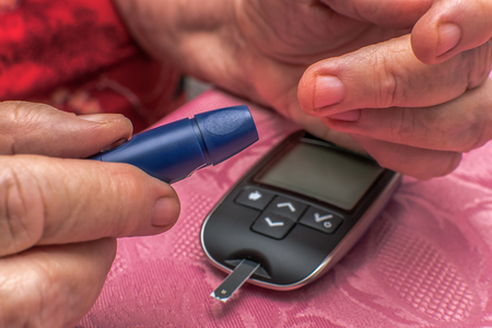 An old woman checking her blood sugar level. The focus is on the hand and the device. Concept: Healthcare, people and medicine