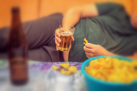 A fat man suffers from overweight and eats chips, drinks alcohol and looks in the phone. Concept: Healthcare