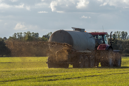 A farm tractor sprays its manure from the tanker onto a field. Manure is used as fertilizer in agriculture. Concept: agriculture Stockfoto