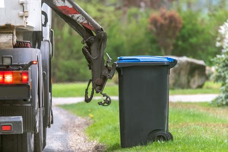 Smaltimento rifiuti urbani. Con uno speciale camion della spazzatura per auto, la spazzatura dal bidone della spazzatura viene caricata nell'auto. Concetto: Smaltimento e pulizia dei rifiuti
