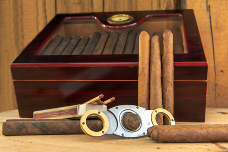 Time to enjoy! Quality cigars and other accessories such as cigar cutters, matches and cigar cases on a wooden table. In the background a humidor in the front of a wooden wall. Concentrate on the cigars. C