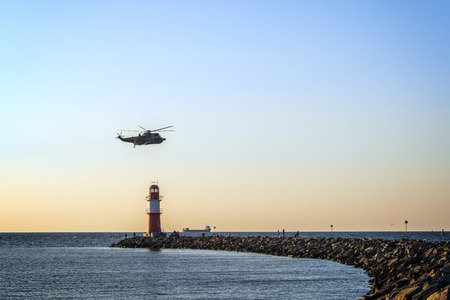 A military helicopter flies over a lighthouse at the harbor entrance in Warnem?nde on the Baltic Sea. Concept: travel and vacation 版權商用圖片