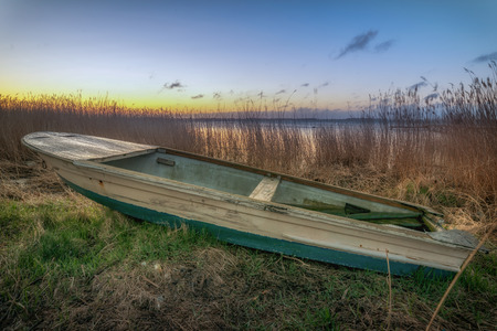 A rowing boat reads in the reeds ashore. Concept: postcards or vacation and travel