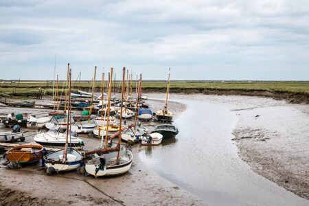 Small sail boats moored at Blakeney Harbour in Norfolk during low tide on a cloudy Summer day.