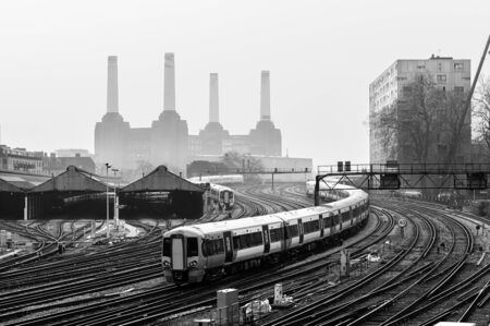 Moving local trains and railway tracks in London, with Battersea Power Station to be recognized behind the fog in the background. Black and White.