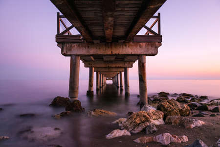 Pink sunset as seen from below an old wooden jetty on a beach in the Costa del Sol in Marbella, Spain. Long exposure. Stock Photo